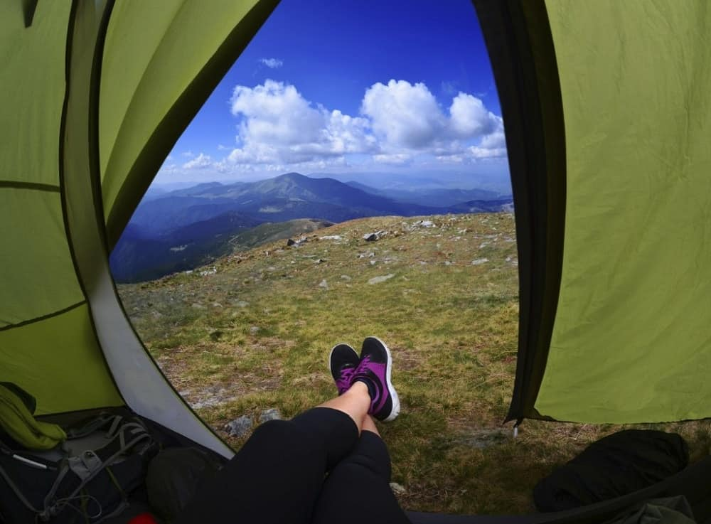 A woman lying in a tent with a view of mountains and the sky.