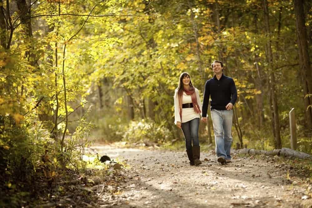 A couple walking outside with the sun shining through the trees.