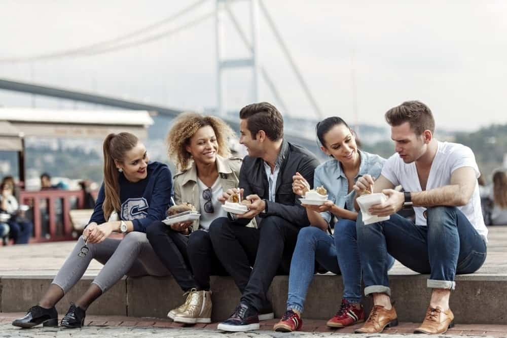 A group of friends eating outside together on the sidewalk.