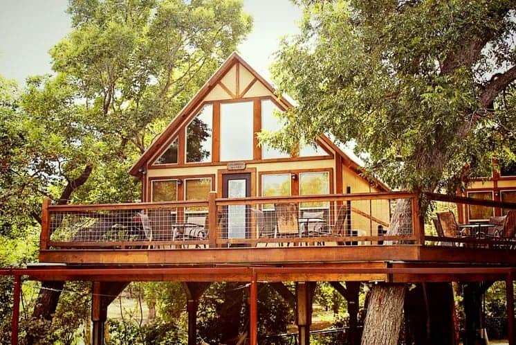 A large wooden treehouse with balcony in Geronimo Creek Retreat in Seguin, Texas.