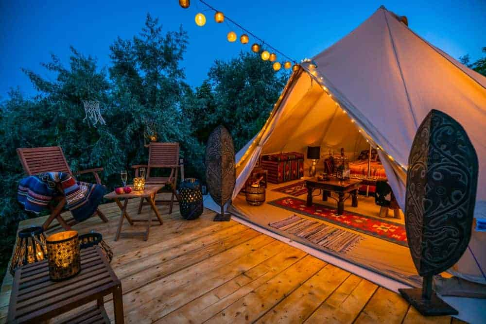 Glamping camping with a semi-furnished tent interior, string lighting, and wood furniture and accessories.