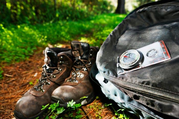 Hiking gear on a trail with books, pack, compass.