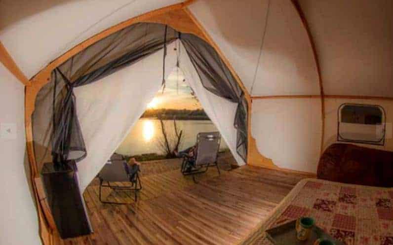 The interior of a lakefront safari tent.