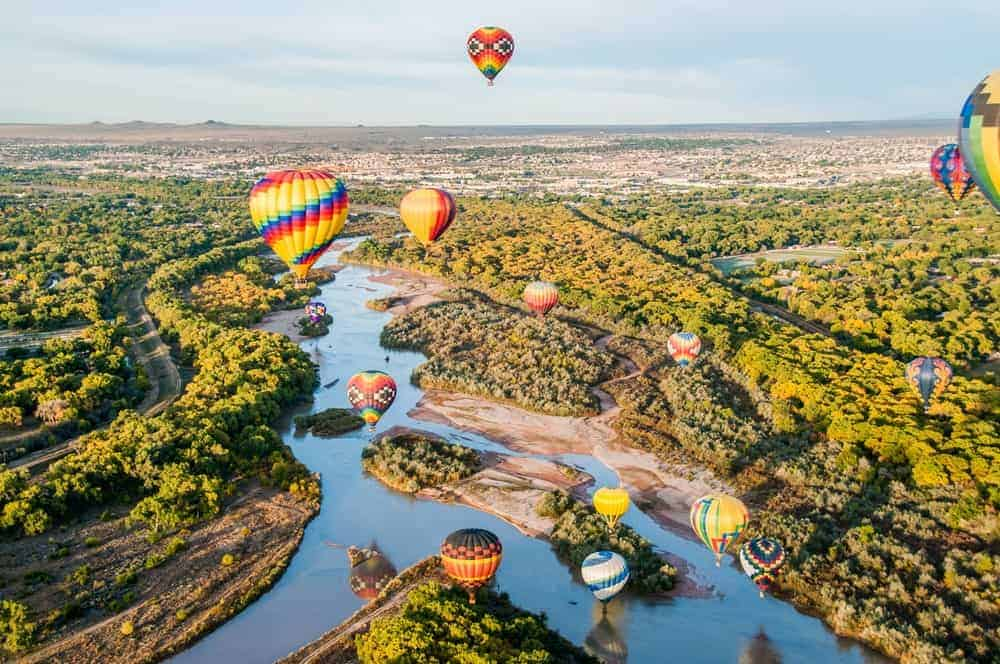 Aerial view of New Mexico landscape with hot air balloons flying over it.