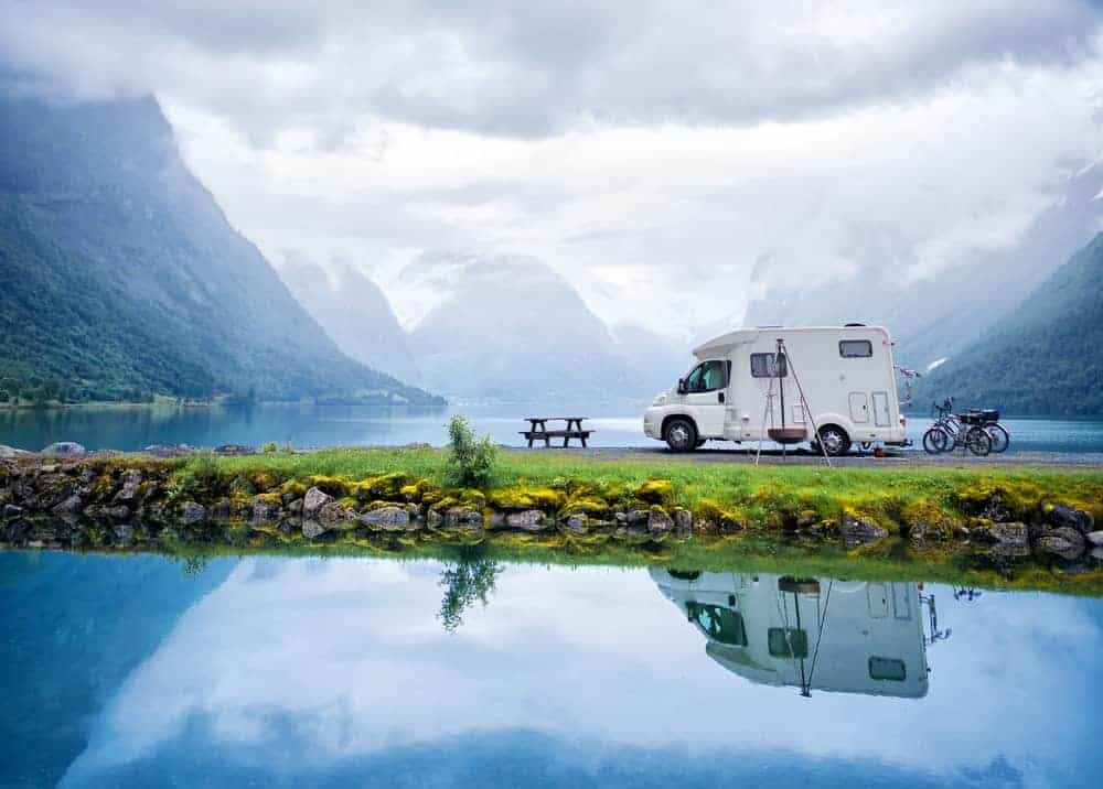 RV parked at a stunning lake and mountain scenery.