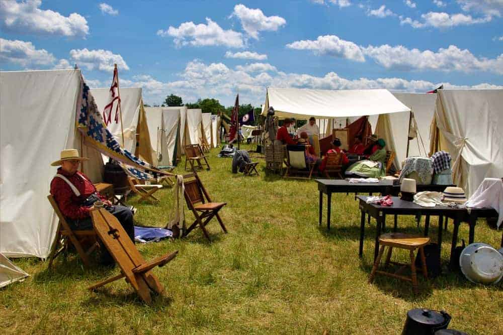 Reenactment Campers with white tents and wooden furniture.