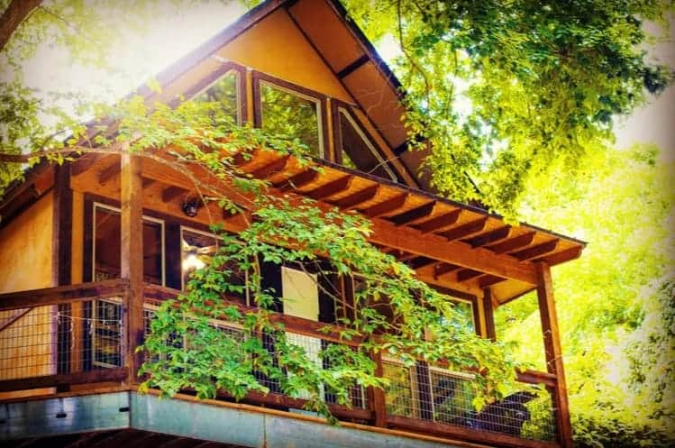 A wooden treehouse with balcony in River Road Tree Houses, New Braunfels.