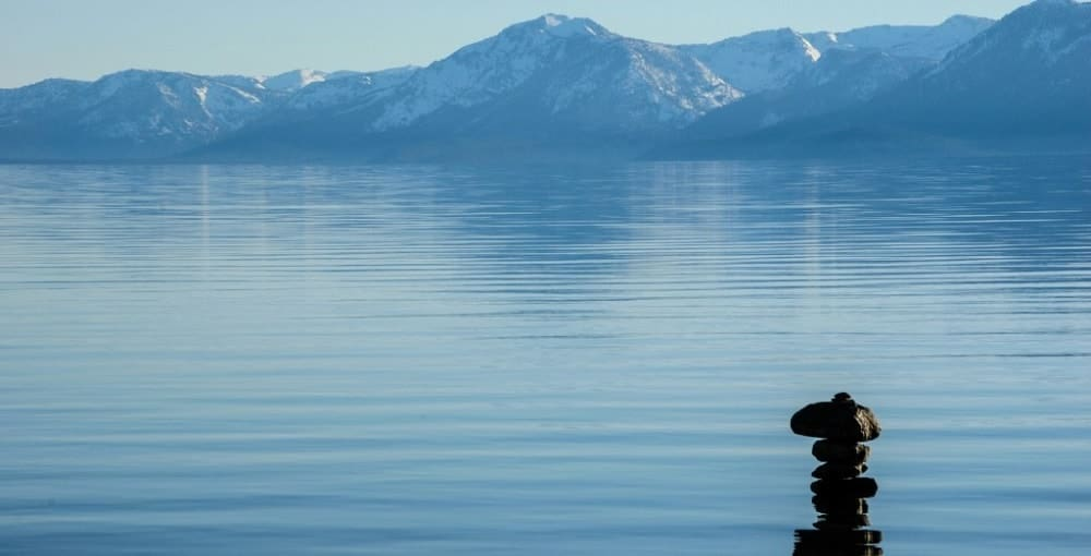 Rocks stacked in a serene lake representing outside therapy.