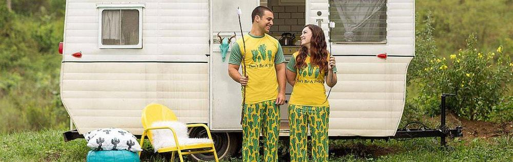 A young couple in matching outfit each holding a stick with marshmallow and standing in front of a small trailer.