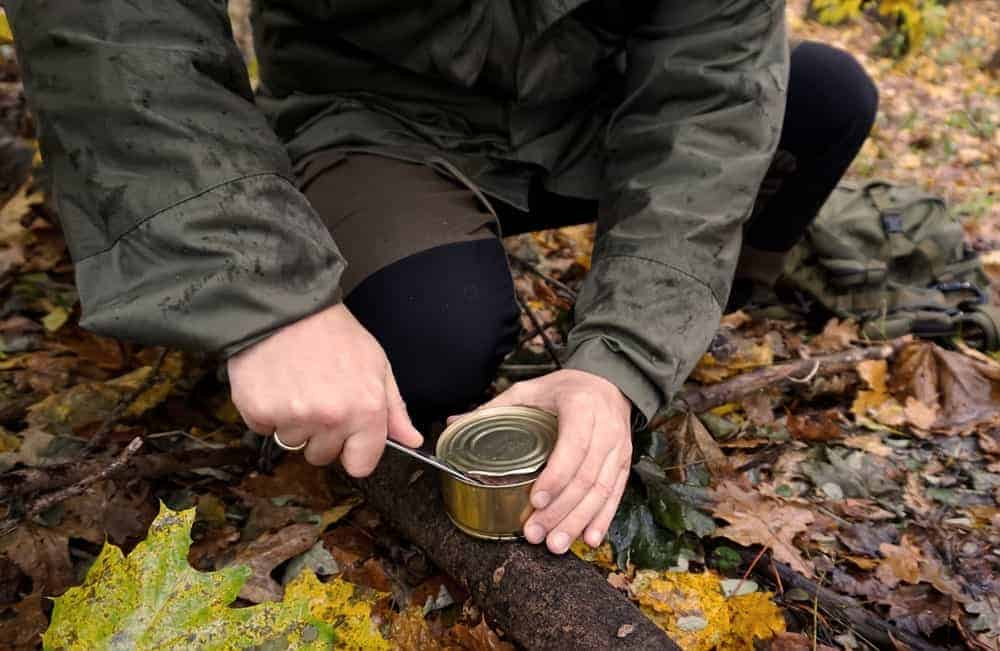 A survivalist camper opening a canned food with a knife.
