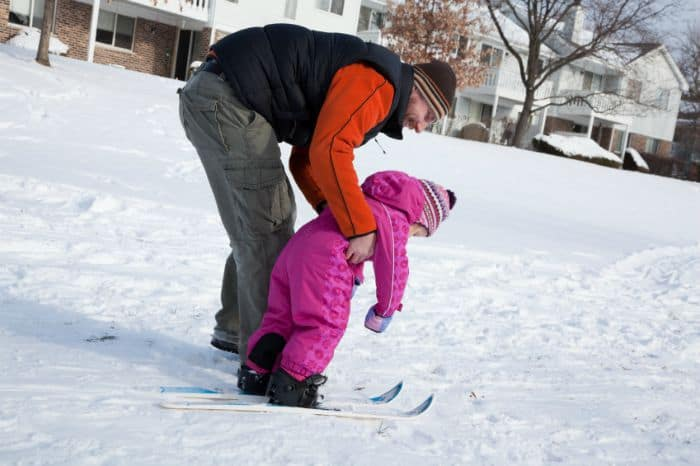 A parent teaching his kid how to ski.