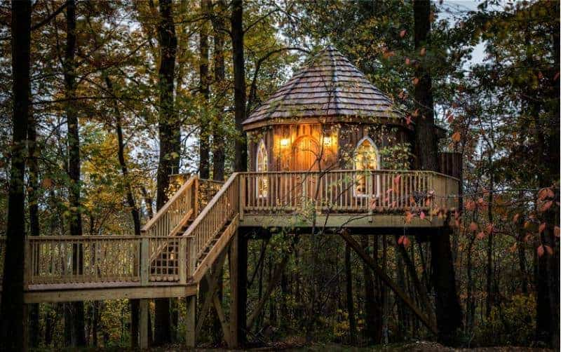A tree house with lights and a wooden elevated walkway.
