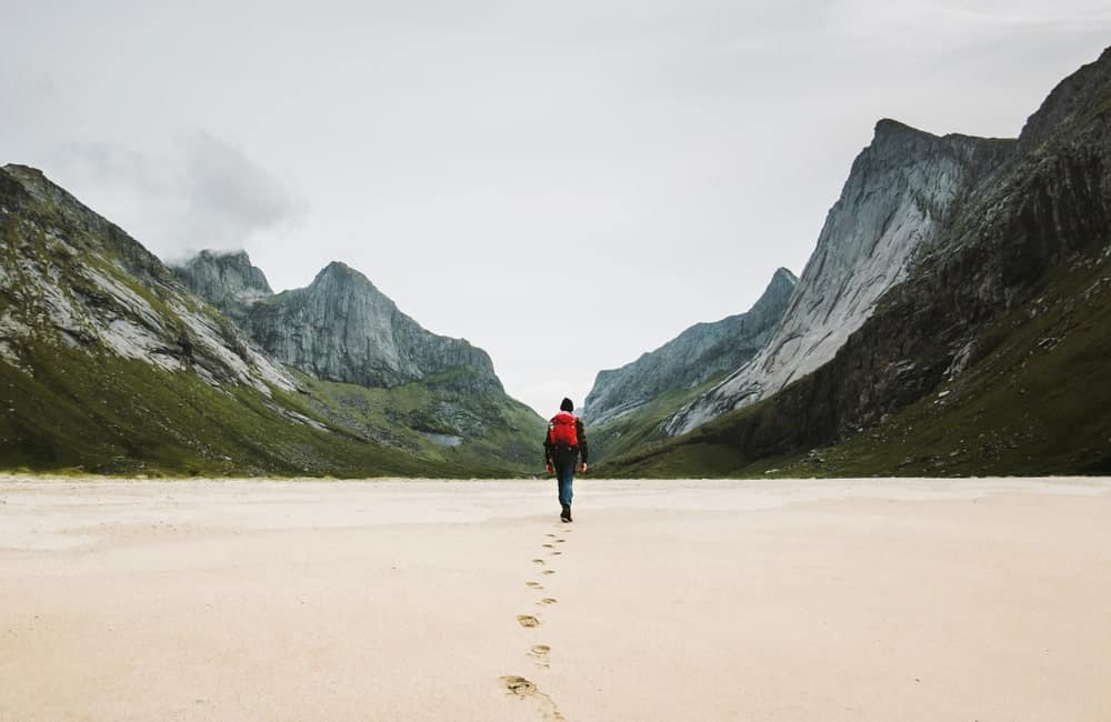 Man ultralight backpacking and leaving footprints on the sand as he walks toward the mountains.