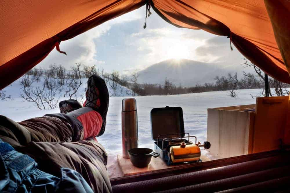 A man camping in winter.