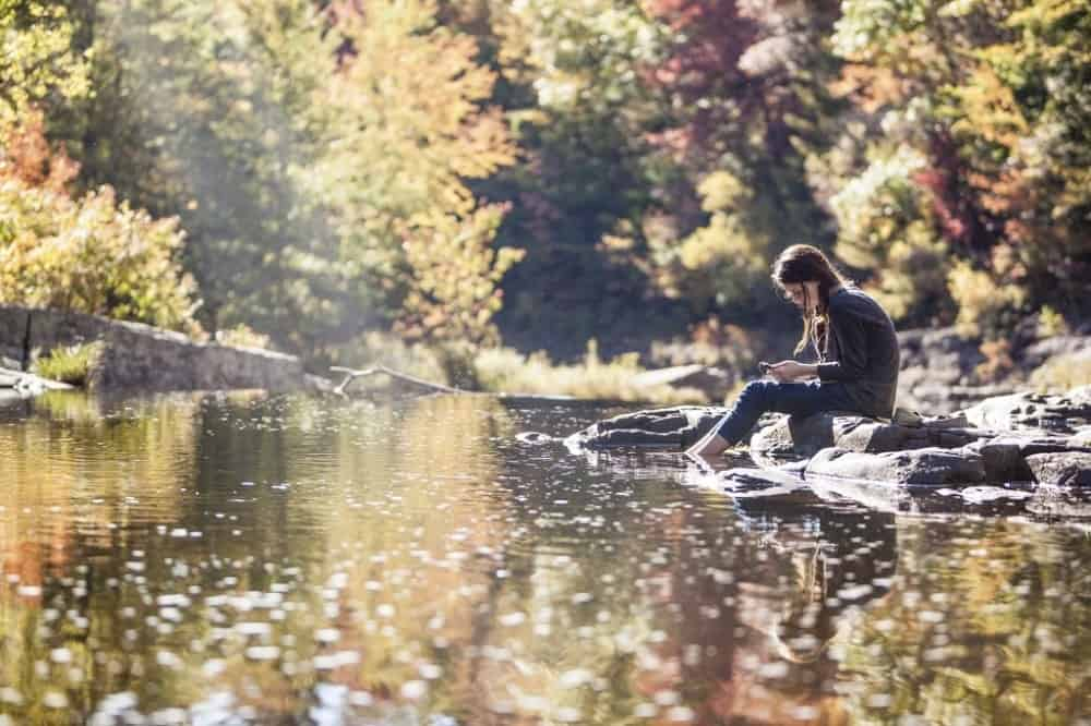 A look at a woman relaxing by the stream with her feet soaked in the water.
