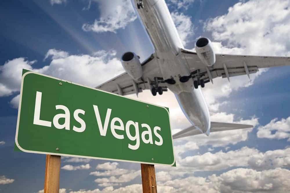 Las Vegas sign with plane flying over it.