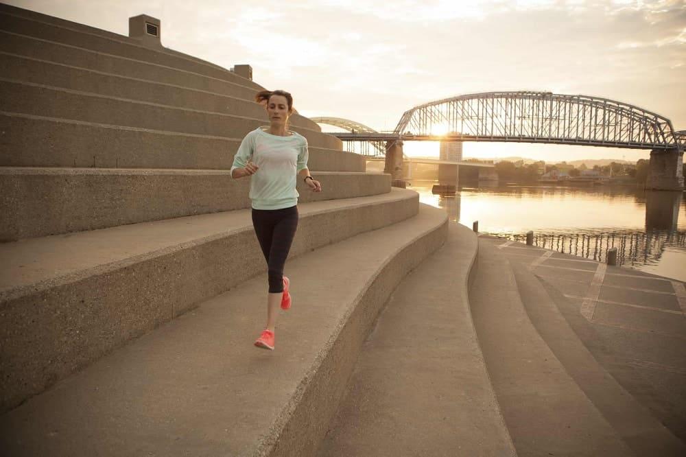 Person jogging in downtown Cincinnati along the river.