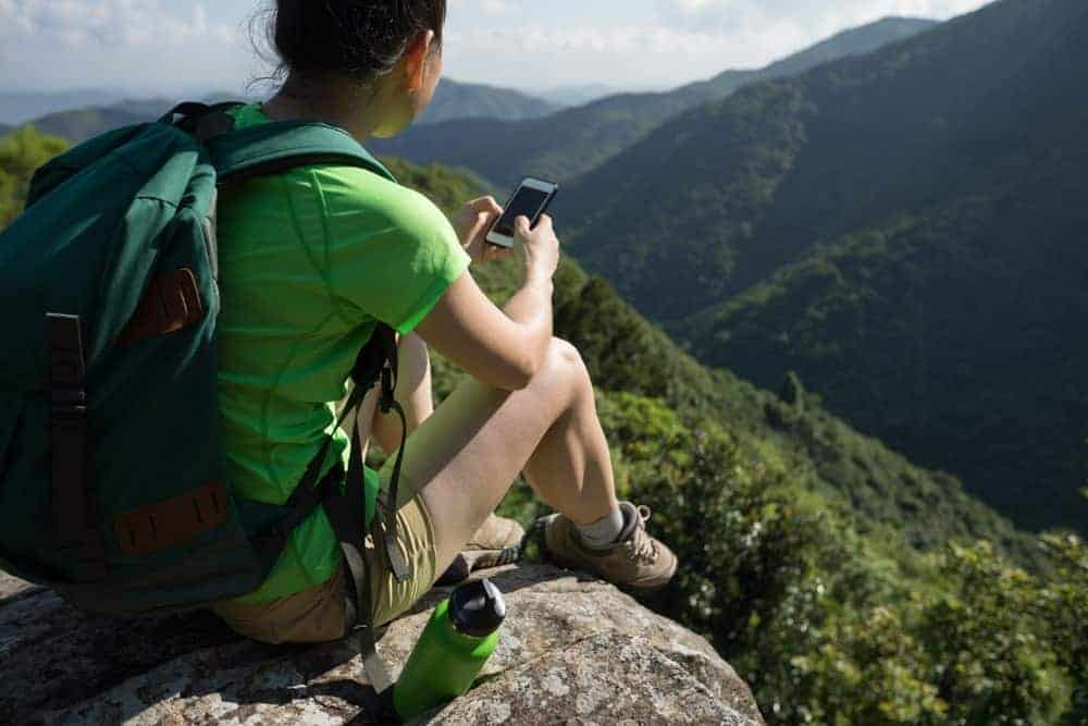 Young woman hiker using a smartphone while sitting on a mountaintop.