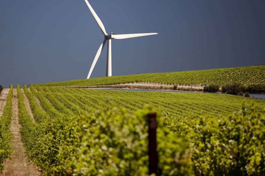 A large wind turbine in the background of a large farm field.