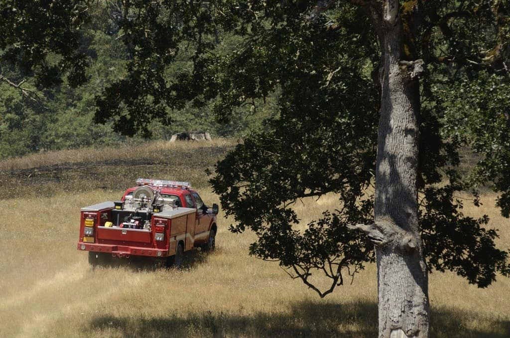 A firefighter rig rushing through the field.