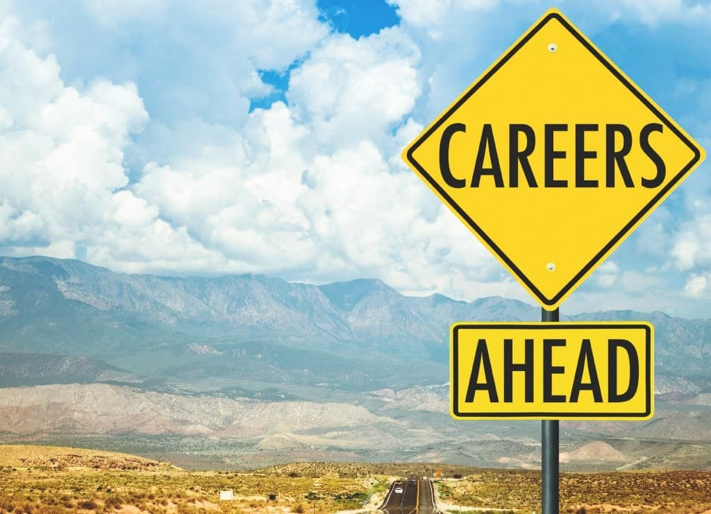 Career ahead sign on the road with mountains in the background.