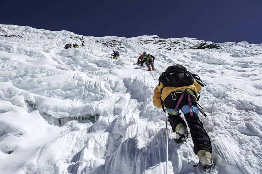 A team of men climbing the ice wall.