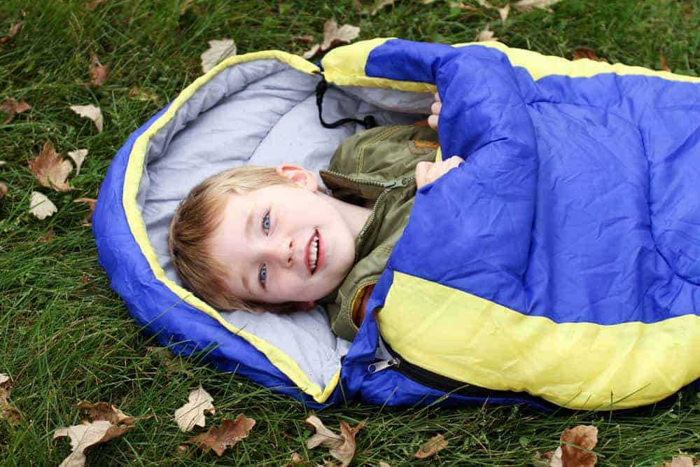 A young kid sleeping in sleeping bag while camping.