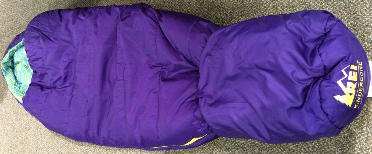 A purple REI Kindercone sleeping bag for kids with foot cover.