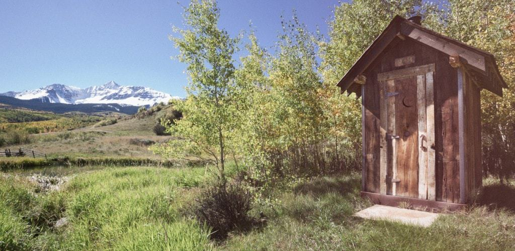 This is a look at a wooden outhouse in a lush landscape.