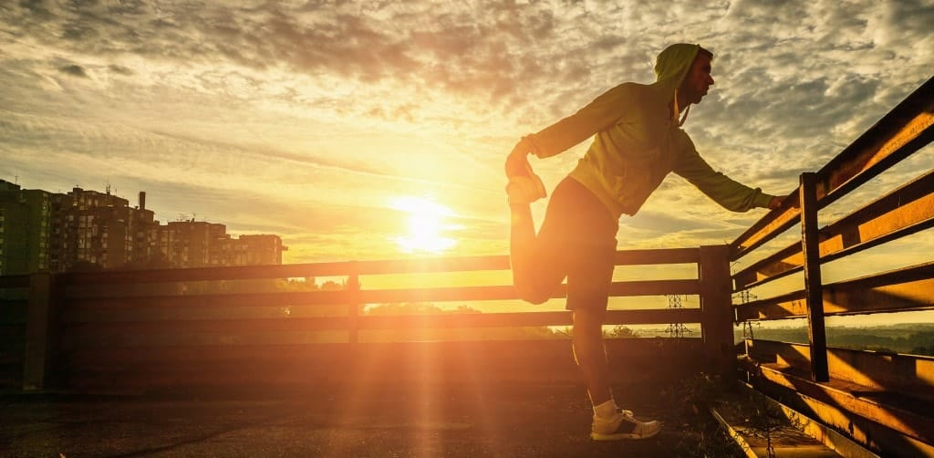 A jogger stretching outside with the sun rising.