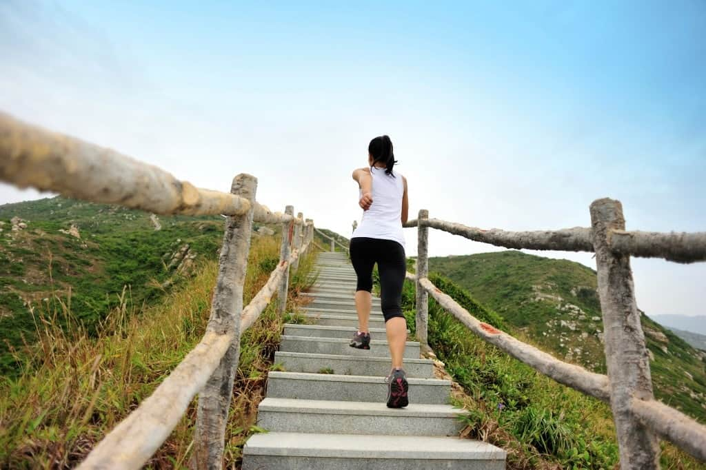 A woman jogging up the stairs.