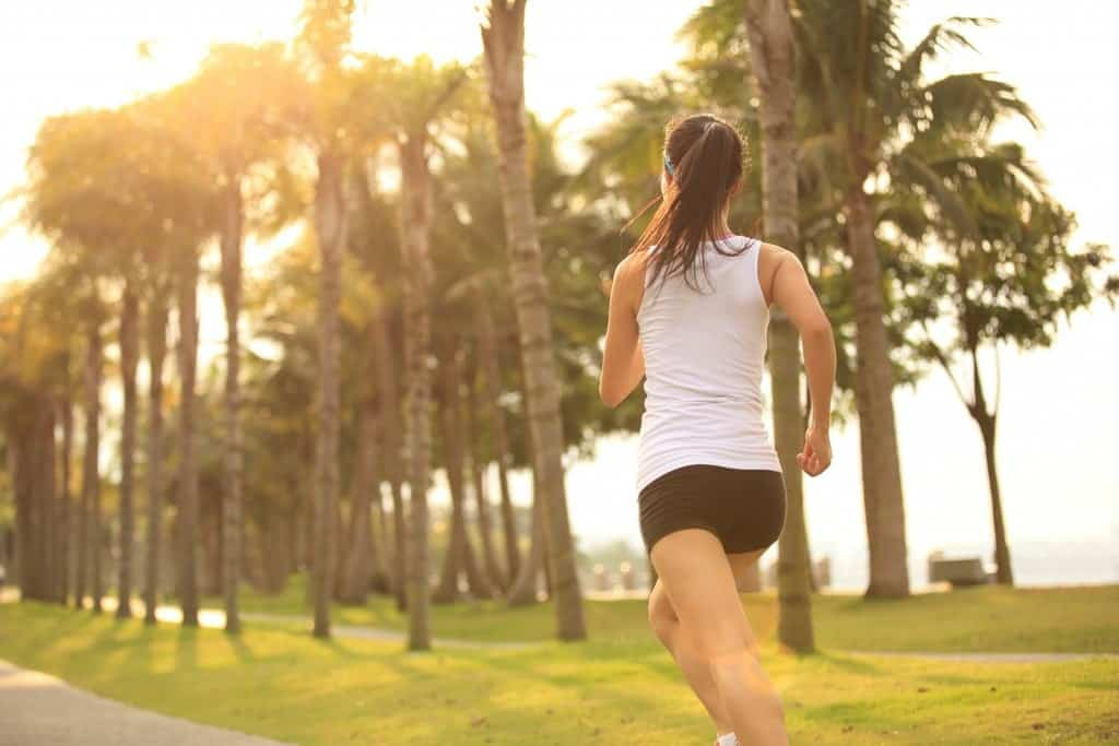 A woman jogging outside at the tree lined street.