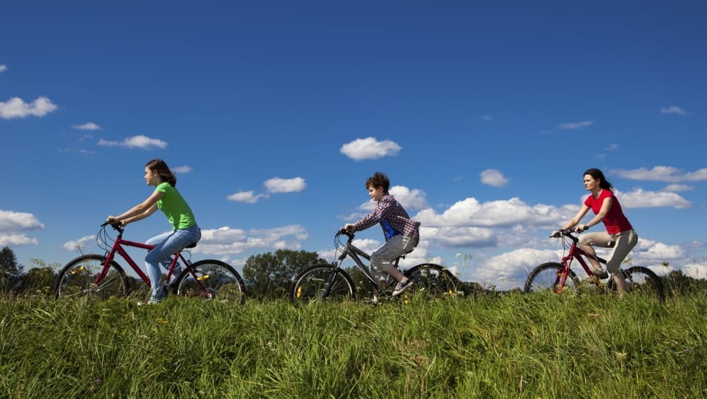 A family biking outdoors by the field of grass.