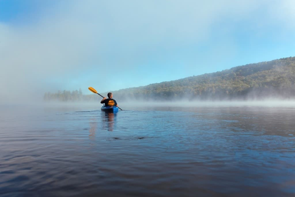 A person kayaking on a lake with low morning fog.