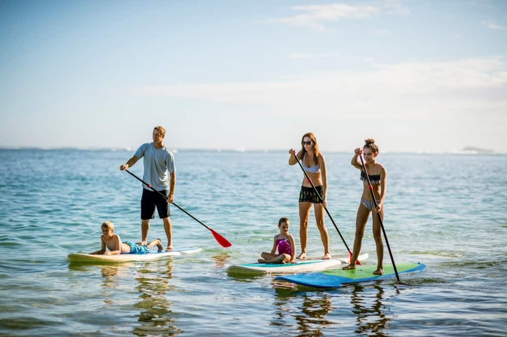 A family on stand up paddle boards with kids on the board.