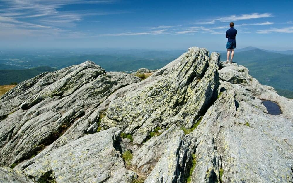 A hiker stands on top of Camel's Hump.