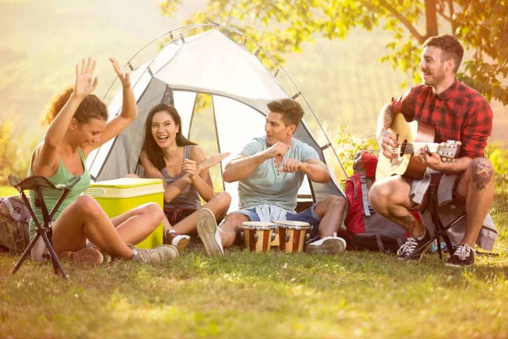 Friends on a camping trip enjoying some music.