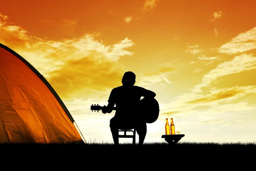 Silhouette of a man with his guitar beside two bottles of beer and his camping tent against the sunset backdrop.