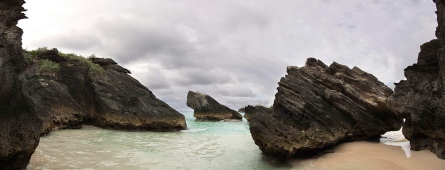 A beach on the south Atlantic side of the island with fine white sand. This section of beach has large water-weathered boulders. Even on a rare cloudy day, the waters are clear and calm. These rocks have a much more jagged appearance than other boulders on the beaches to come. The name of the beach refers to the shape of the shore.