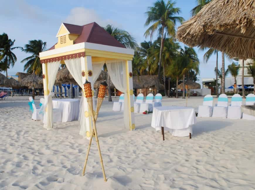 A popular tourist beach with high-rise luxury hotels and an enormous shopping district nearby. Pictured here is the white sand shore decorated for a destination wedding on the beach. The beach umbrellas and shacks along the beach are all palm roofed.