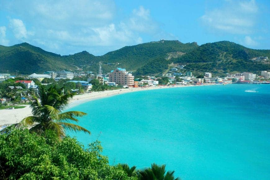 The Great Bay Beach of Sint Maarten is a tourist beach near the capital of Sint Maarten. The shallow waters extend far off the shore and are decadently warm and relaxing. This view from above the beach shows the curve and the buildings along the coast.