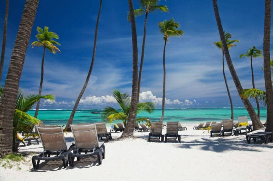 The shores of Punta Cana in the Dominican Republic are a popular tourist destination amongst the cane palms. Seen here are the shallow shores near the white sand beach. The area is popular for whale watching, discovery cruises, sport fishing, and swimming with dolphins.