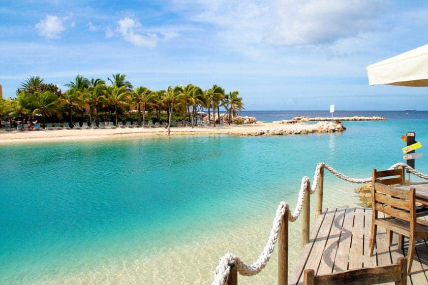 The popular tourist beach has crystal clear blue waters. The curved shore, shown here from one of the docks, is lined by beachside bars, and the beach becomes a lively party scene at night. This beach is also known as Mambo beach.