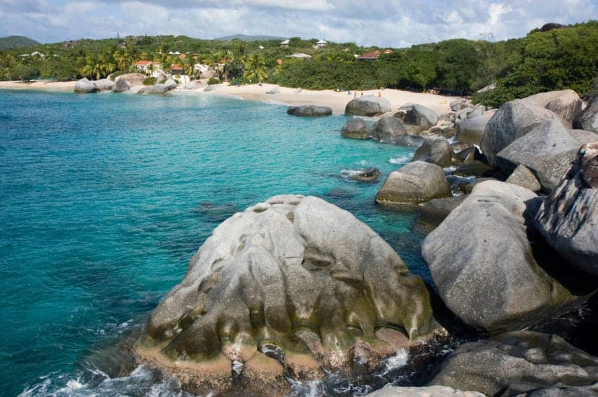 """A view of one of the many beaches of Virgin Gorda, near the large water-weathered rocks of """"The Baths."""" The enormous boulders that dot the beach give this white sanded beach a unique look."""