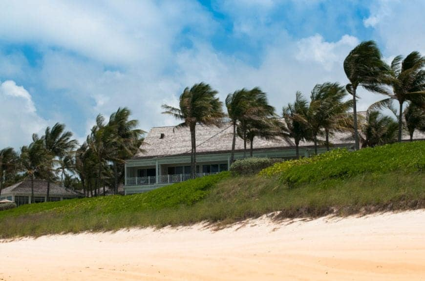 A beautiful white sand beach lined by resort homes and coconut palm trees. The narrow beach is topped by a lush green hill. The soft sand is warmed by the sun, and is delightful to scrunch your toes into.