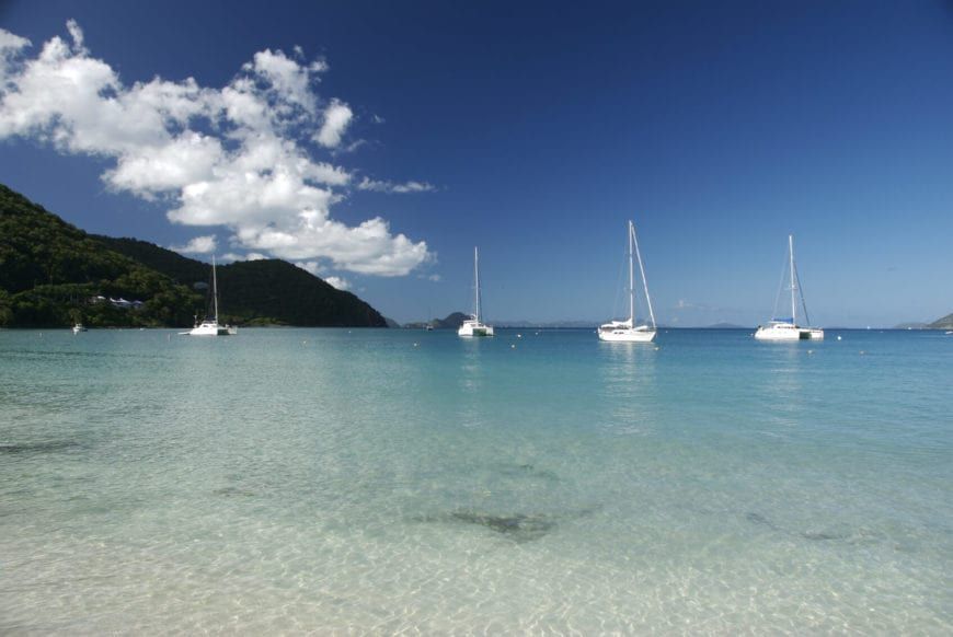 A long white sanded beach protected by a coral reef. The crystal clear water is visible even from the shallows near the sand. Also visible from this angle are the densely forested hills beyond the sailboats.