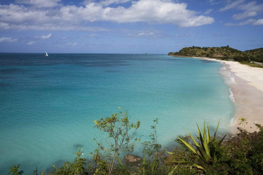 A beautiful resort beach with shallow waters and a narrow beach. Far off the coast is a sailboat, just barely visible, that gives you an idea of just how large the swimming area of this beach is. This photo is taken from on top of one of the lush hills on either side of the bay's beach, and shows the entire length of Galley Bay beach.