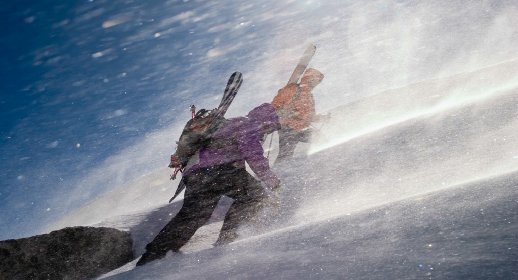 Skiers climbing a mountain in a winter storm.