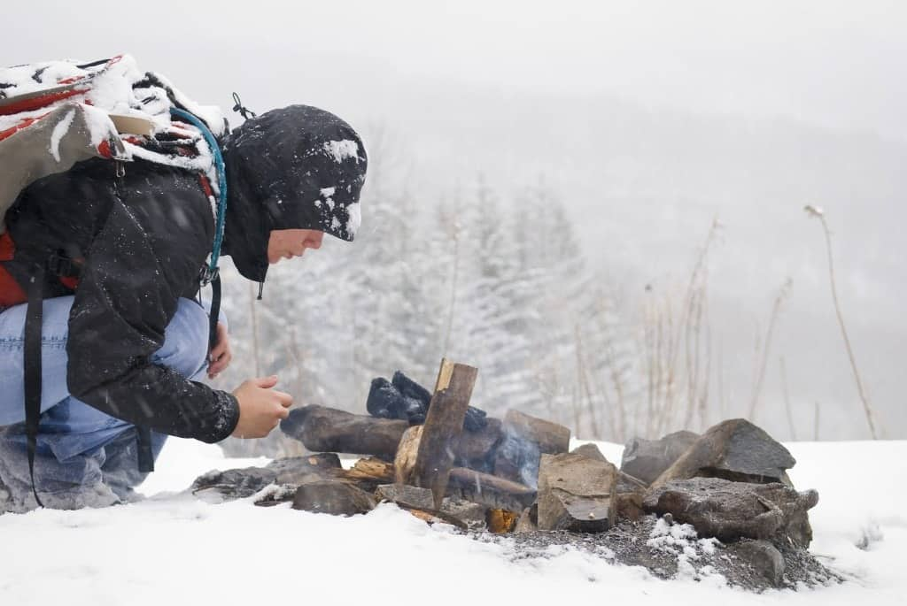 A person starting a fire in the winter landscape.