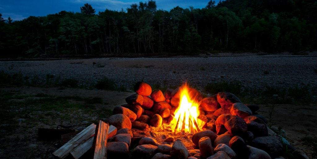 A camp fire with wood next to the stone fire ring.